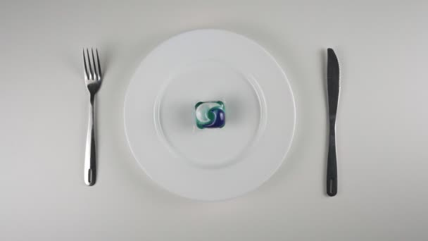 Waschpulverpod auf einem Teller, Waschmittelpod. Vergrößern. Vorbereitung auf den Verzehr einer Kapsel mit Waschmittel, Waschpulver, Internet-Meme. 60 fps