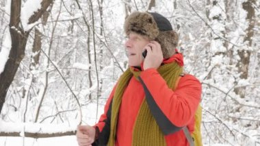 Elderly European man talking on a smartphone in a snowy forest. Thick dense thicket of trees and roots in in the snow-covered forest. Hike and travel concept 60 fps