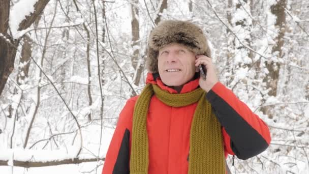 Elderly european smiling man talking on a smartphone in a snowy forest. Thick dense thicket of trees and roots in in the snow-covered forest. Hike and travel concept 60 fps