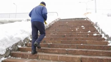 elderly man runs up the stone stairs in winter. sports, cardio. Healthy life concept. 60 fps