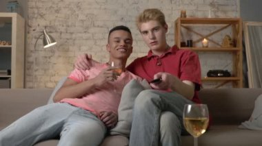 Multinational gay couple sitting on couch, watch TV, use the remote control, look at the camera. Homeliness, romantic evening, hugs, happy LGBT family concept. 60 fps