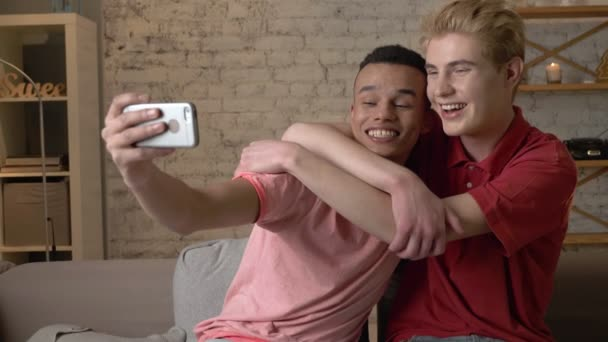 Two international gay friends, sitting on the couch, hugging, making selfies, laughing. Homeliness, romantic evening, background, hugs, happy LGBT family concept 60 fps
