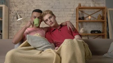 Multinational gay couple sitting on couch covered with a warm blanket, watch TV, use the remote control, look at the camera. Homeliness, romantic evening, cuddles, happy LGBT family concept. 60 fps