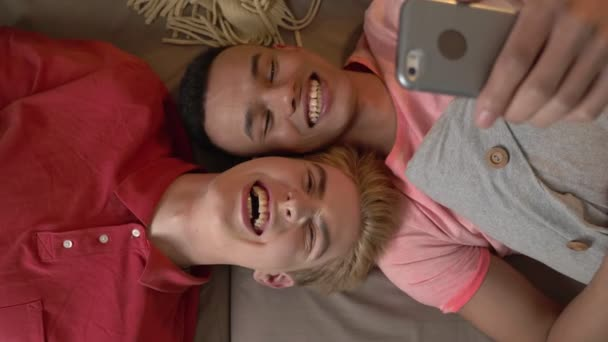 Happy international gay couple is lying on the couch and making selfies on a smartphone. Homeliness, LGBT lovers, happy gay family concept, laughing. 60 fps
