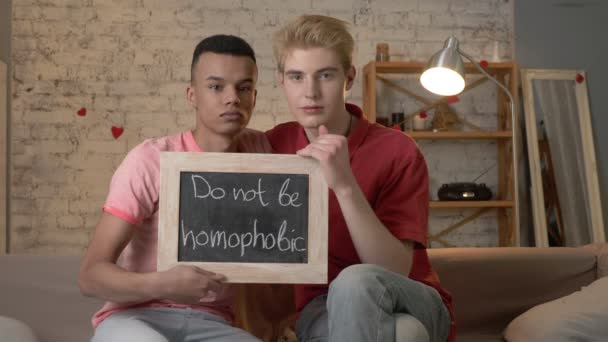 A sad international gay couple is sitting on the couch and holding a sign. Do not be homophobic. Look at the camera. Home comfort on the background. 60 fps