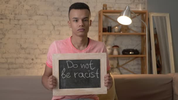 A sad African guy sits on the couch and holds a sign. Do not be racist. Anti-racism, national inequality concept. Look at the camera. 60 fps