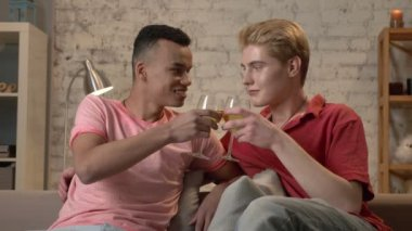 Multinational gay couple sitting on a sofa, clinking glasses and drinking wine. LGBT lovers, boys, young friends, happy gay family concept. 60 fps