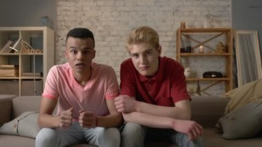 Two gay guys are sitting on the couch and watching TV, emotion of waiting and disappointment, sadness, crying. LGBT lovers, happy gay family, home cosiness concept. Look at the camera 60 fps