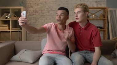Two multi-ethnic homosexual friend sitting on the couch, embracing and showing a greeting gesture in a video chat. Happy LGBT couple concept, gay lovers. 60 fps