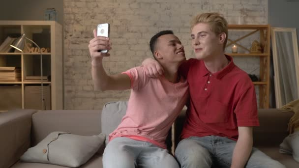 Two multiethnic homosexual friends sit on the couch, embrace and do selfie. Happy LGBT couple concept, gay lovers. 60 fps