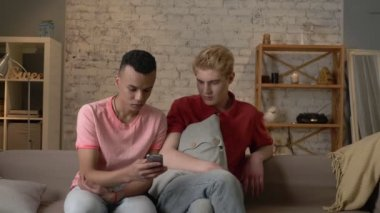 Two international friends of a homosexual are sitting on the couch and watching disgusting, mercenary pictures on a smartphone. Home cosiness, family, internet concept. 60 fps