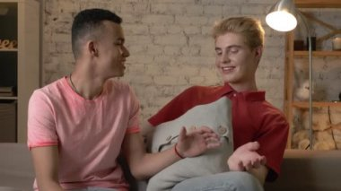 Two multinational homosexual friends sit on the couch shaking hands, making peace, embracing like brothers. Home cosiness, family, internet concept. 60 fps