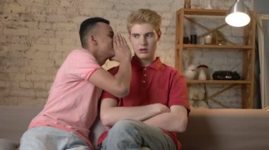 Two young homosexual boys are sitting on the couch, african guy with short hair tells the secrete to his partner, the blonde is shocked 60 fps
