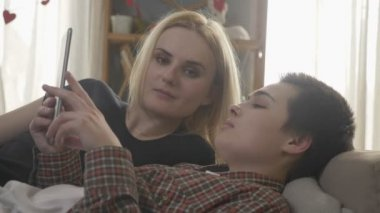 Lesbian couple is resting on the couch, using tablet computer, scrolling photos on tablet, family idyll, love, cute, close up. 60 fps