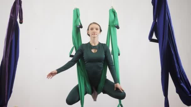 Mladá Kavkazský žena dělat antigravitační fly jóga cvičení v houpací síti ve studiu doma. Letecká aero překrýt fitness trenér cvičení. Medituje, harmonii a vyrovnanosti koncept 60 fps