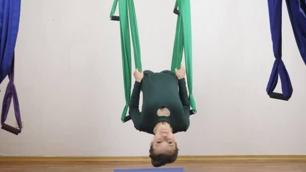 Mladá Kavkazský žena dělat antigravitační fly jóga cvičení v houpací síti ve studiu doma. Letecká aero překrýt fitness trenér cvičení. Layback v pozici kříž medituje, harmonii a vyrovnanost