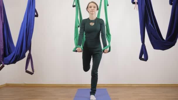 Mladá Kavkazský žena dělat antigravitační fly jóga cvičení v houpací síti ve studiu doma. Letecká aero překrýt fitness trenér cvičení. Lonž, motouzy, split, medituje, harmonii a vyrovnanosti koncept, přední