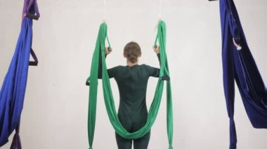 Young caucasian woman making antigravity fly yoga exercises in hammock in studio indoors. Aerial aero fly fitness trainer workout. Vertical plank upside down. Meditates, harmony and serenity concept