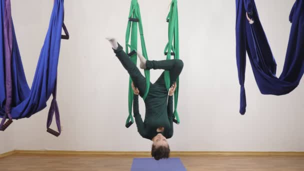 Young caucasian woman making antigravity fly yoga exercises in hammock in studio indoors. Aerial aero fly fitness trainer workout. Eagle Pose upside down. Meditates, harmony and serenity concept