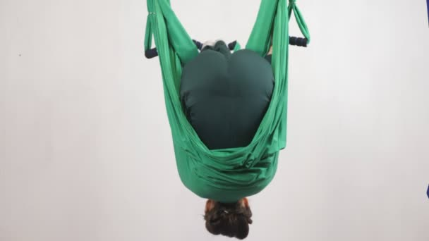 Young caucasian woman making antigravity fly yoga exercises in hammock in studio indoors. Aerial aero fly fitness trainer workout. Somersault, roll, meditates, harmony and serenity concept, back side