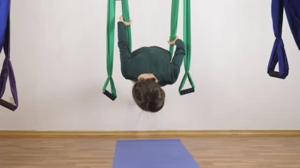 Mladá Kavkazský žena dělat antigravitační fly jóga cvičení v houpací síti ve studiu doma. Letecká aero překrýt fitness trenér cvičení. Vodorovná prkna. Medituje, harmonii a vyrovnanosti koncept, zblizka
