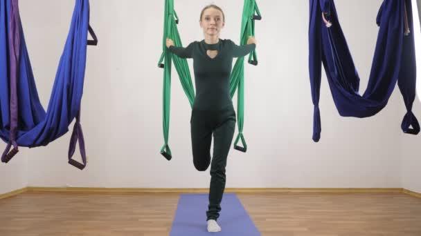 Mladá Kavkazský žena dělat antigravitační fly jóga cvičení v houpací síti ve studiu doma. Letecká aero překrýt fitness trenér cvičení. Vysoký výpad. Medituje, harmonii a vyrovnanosti koncept 60 fps