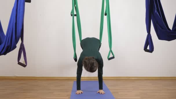 Mladá Kavkazský žena dělat antigravitační fly jóga cvičení v houpací síti ve studiu doma. Letecká aero překrýt fitness trenér cvičení. Prkno s nohama v houpací síti. Medituje, harmonii a vyrovnanost