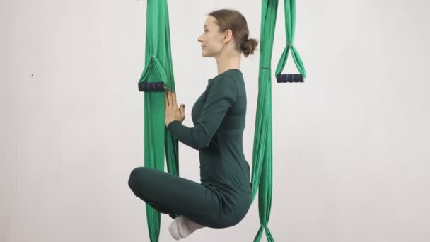 Young caucasian woman making antigravity fly yoga exercises in hammock in studio indoors. Aerial aero fly fitness trainer workout. Lotus pose, meditates, harmony and serenity concept, side view, close