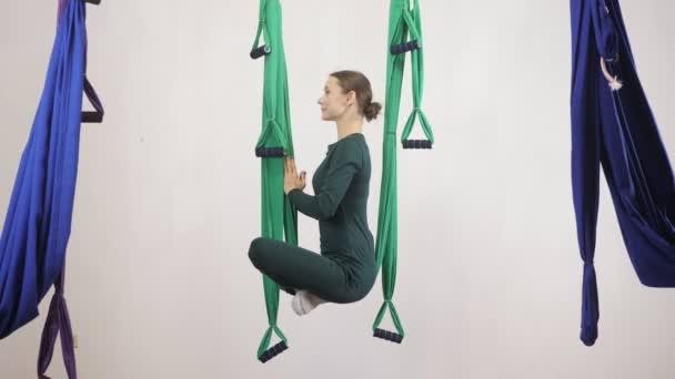 Mladá Kavkazský žena dělat antigravitační fly jóga cvičení v houpací síti ve studiu doma. Letecká aero překrýt fitness trenér cvičení. Lotus pose, medituje, harmonii a vyrovnanosti koncept, boční pohled 60 fps