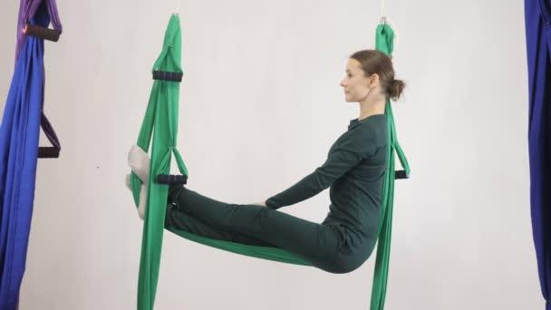 Mladá Kavkazský žena dělat antigravitační fly jóga cvičení v houpací síti ve studiu doma. Letecká aero překrýt fitness trenér cvičení. Židle v pozici kříž, medituje, harmonii a vyrovnanosti koncepce
