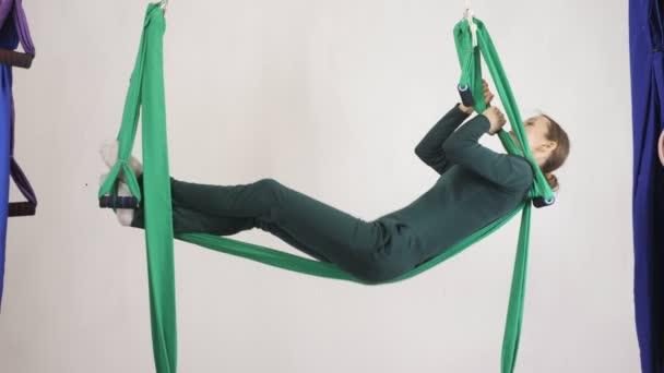 Mladá Kavkazský žena dělat antigravitační fly jóga cvičení v houpací síti ve studiu doma. Letecká aero překrýt fitness trenér cvičení. Layback póza, medituje, harmonii a vyrovnanosti koncept, pohled 60