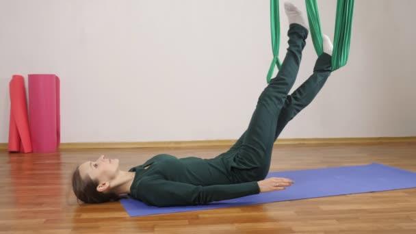 Mladá Kavkazský žena dělat antigravitační fly jóga cvičení v houpací síti ve studiu doma. Letecká aero překrýt fitness trenér cvičení. Layback s nohama v houpací síti, medituje, harmonii a vyrovnanost