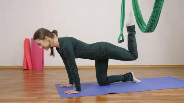Mladá Kavkazský žena dělat antigravitační fly jóga cvičení v houpací síti ve studiu doma. Letecká aero překrýt fitness trenér cvičení. Superman pozice s nohama v houpací síti, medituje, harmonie a