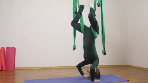 Young caucasian woman making antigravity fly yoga exercises in hammock in studio indoors. Aerial aero fly fitness trainer workout. Reclining Angle Pose, meditates, harmony and serenity concept, side