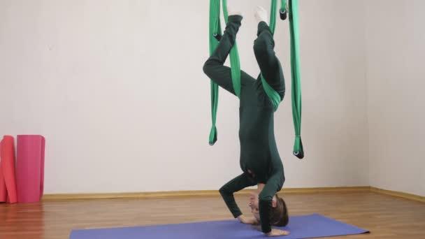 Mladá Kavkazský žena dělat antigravitační fly jóga cvičení v houpací síti ve studiu doma. Letecká aero překrýt fitness trenér cvičení. Sklápěcí úhel představovat, medituje, harmonii a vyrovnanost koncept, boční