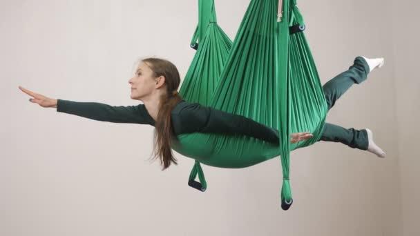Mladá Kavkazský žena dělat antigravitační fly jóga cvičení v houpací síti ve studiu doma. Letecká aero překrýt fitness trenér cvičení. Superman póza, medituje, harmonii a vyrovnanosti koncept, pohled 60