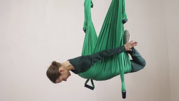 Young caucasian woman making antigravity fly yoga exercises in hammock in studio indoors. Aerial aero fly fitness trainer workout. Bow Pose. Meditates, harmony and serenity concept, side view 60 fps