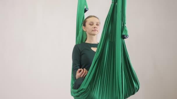 Mladá Kavkazský žena dělat antigravitační fly jóga cvičení v houpací síti ve studiu doma. Letecká aero překrýt fitness trenér cvičení. Lotus pose, medituje, harmonii a vyrovnanost koncept, pohled zepředu 60
