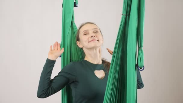 Young woman sits on a hammock smiling stretch out hands and yawing. Aerial aero fly fitness trainer workout. Meditates, harmony and serenity concept, 60 fps