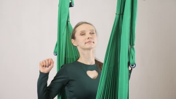 Young woman sits on a hammock smiling stretch out hands. Aerial aero fly fitness trainer workout. Meditates, harmony and serenity concept, 60 fps