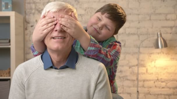 Young fat child closes his grandfathers eyes with his hands. Guess who. A game, prank. Grandson looks into the camera and makes funny faces. Happy family concept 60 fps