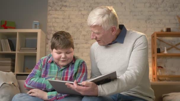 Starší muž učí mladý Tlustý chlap, jak číst. Dědeček a vnuk, Rodina, domácí útulnosti koncept. 60 snímků za sekundu