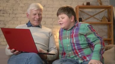 Grandfather and grandson are sitting on the couch and watching a funny movie on the laptop, laughing, speaking. Home comfort, family idyll, cosiness concept, difference of generations 60 fps