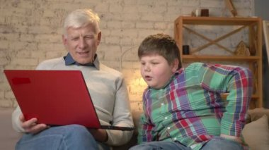 Grandfather and grandson are sitting on the couch and watching a funny, interesting movie on the laptop, laughing. Home comfort, family idyll, cosiness concept, difference of generations 60 fps