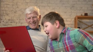 Grandfather and grandson are sitting on the couch and watching a funny movie on the laptop, laughing, speaking. Home comfort, family idyll, cosiness concept, difference of generations. Close up 60 fps