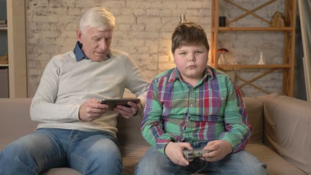 Grandfather and grandson are sitting on the couch. An old man uses a tablet, a young fat guy plays on the console game. Video games. Home comfort, family idyll, cosiness concept, difference of