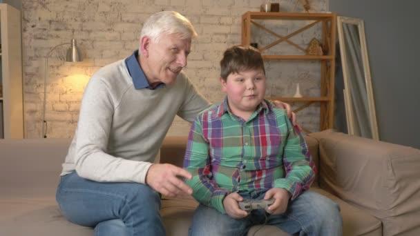 Opa genießt den Sieg seines Enkels im Konsolenspiel. sitzt der alte Mann mit einem dicken Jungen auf der Couch. Videospiel. Wohnkomfort, familiäre Idylle, Gemütlichkeit Konzept, Differenz von