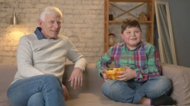 Grandfather and his grandson are sitting on the couch and watching television, fat boy offers grandfather to eat chips, he does not agree. Home comfort, family idyll, cosiness concept, difference of