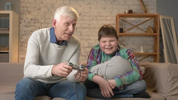 Grandpa plays in the console video game sitting on the couch with his grandson. An elderly man sits on the couch and holds game controller playing video games. Home comfort, family idyll, cosiness