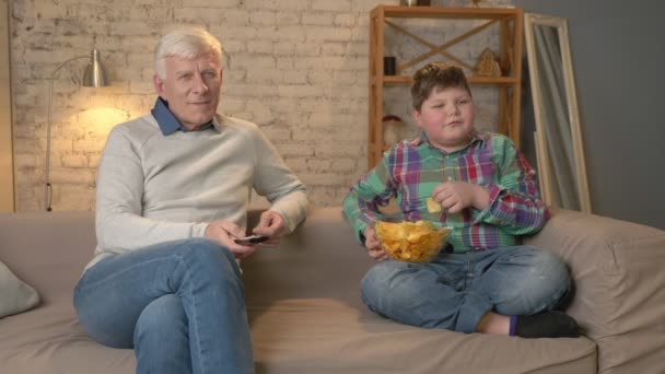 Grandfather and his grandson are sitting on the couch and watching television, eating chips. An elderly man switches channels, uses a remote control. Home comfort, family idyll, cosiness concept